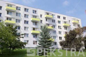 Celkový pohled na bytový dům s balkony a zástěnou a stříškou